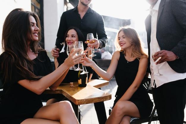 Adorables mujeres tintinean vasos en fiesta y sonriendo