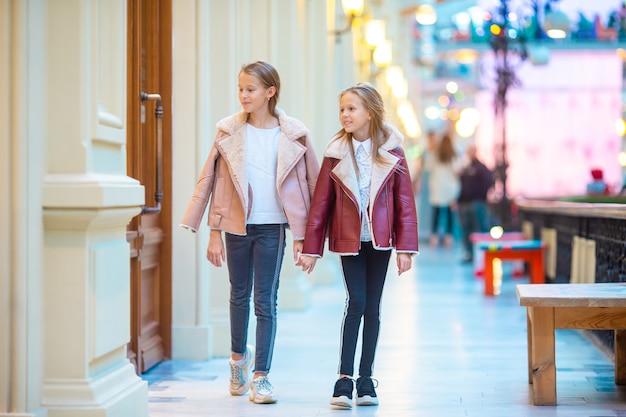 Adorables niñas de compras en el centro comercial