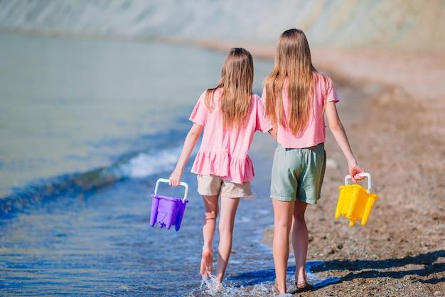 Adorables niñas divirtiéndose en la playa