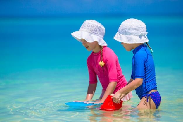 Adorables niñas felices divertirse en aguas poco profundas en vacaciones en la playa
