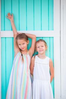 Adorables niñas en el fondo de vacaciones de verano tradicional colorida casa caribeña
