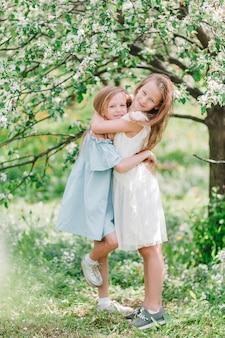 Adorables niñas en jardín floreciente de manzano en primavera