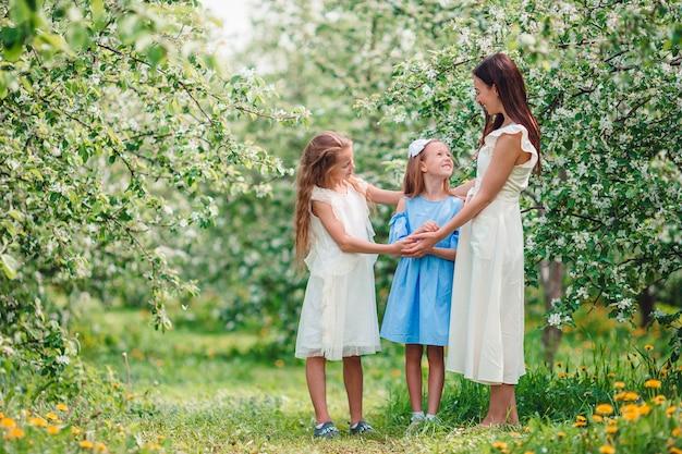 Adorables niñas con joven madre en jardín de cerezos en flor en el hermoso día de primavera