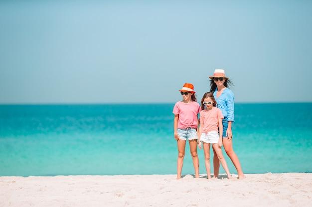 Adorables niñas y joven madre en playa blanca