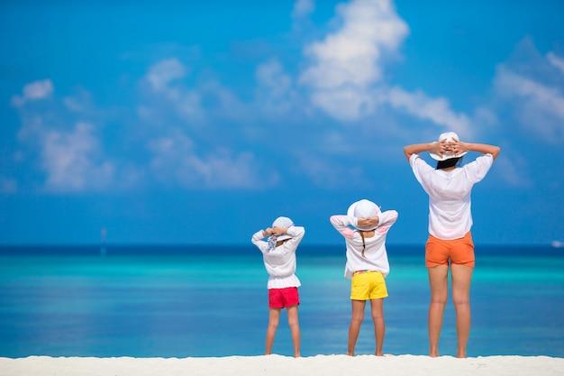Adorables niñas y joven madre en tropical playa blanca