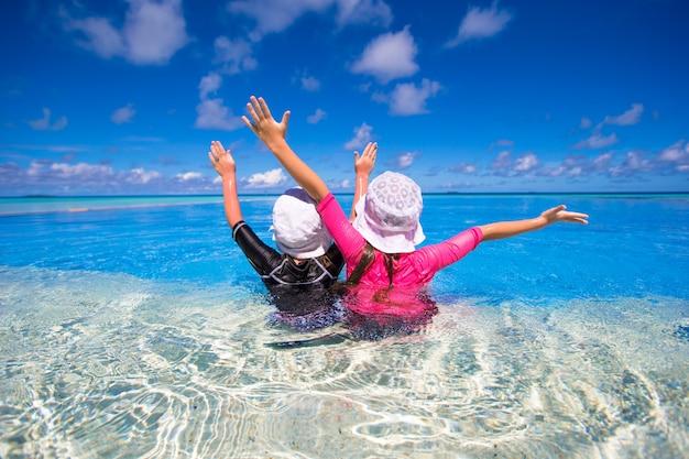 Adorables niñas jugando en la piscina al aire libre