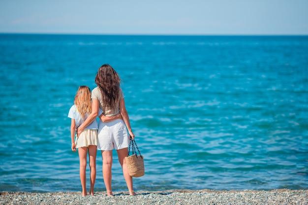Adorables niñas y madre joven en playa blanca tropical