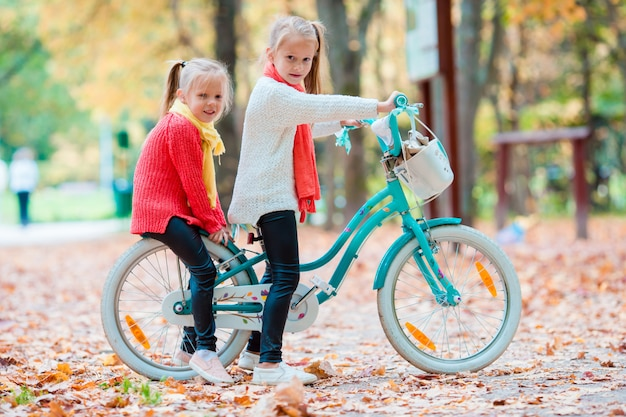 Adorables niñas montando una bicicleta en el hermoso día de otoño al aire libre