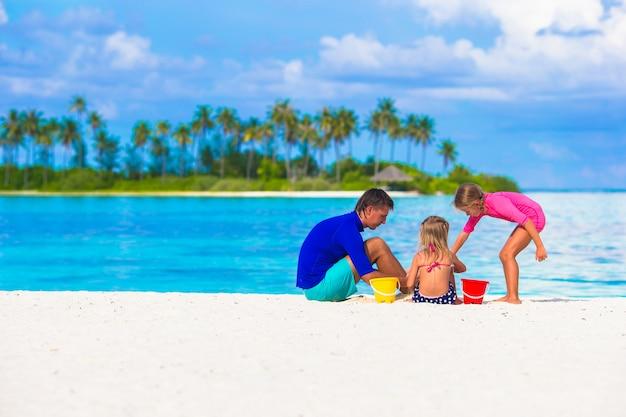 Adorables niñas y papá jugando con juguetes de playa en vacaciones de verano