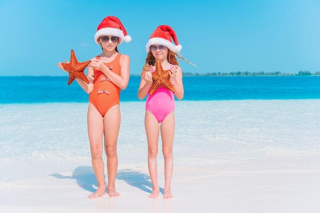 Adorables niñas con sombreros de santa con estrellas de mar en la playa vacía blanca.