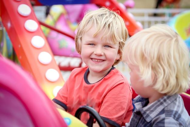 Adorables niños australianos rubios sentados en atracción para niños