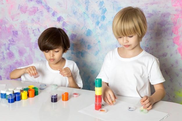 Adorables niños con camisetas blancas jugando con pinturas multicolores