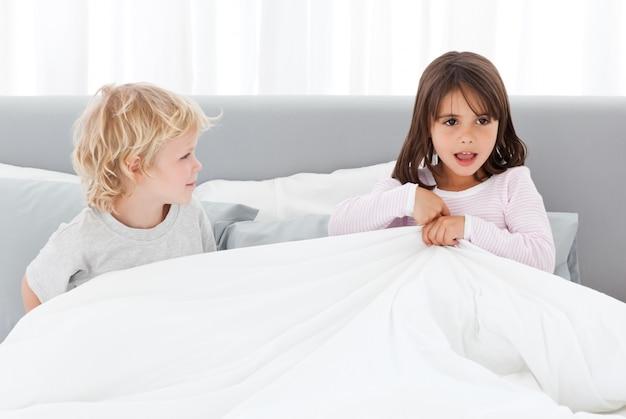 Adorables niños jugando juntos en la cama de sus padres