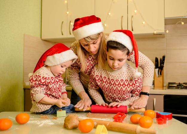 Adorables niños y madre cocinando galletas de navidad en casa. madre e hijos haciendo casa de jengibre