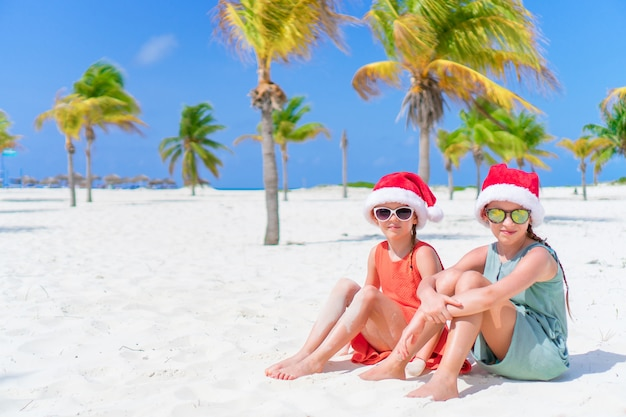Adorables niños pequeños con sombrero de santa durante las vacaciones de navidad en la playa. año nuevo en la playa