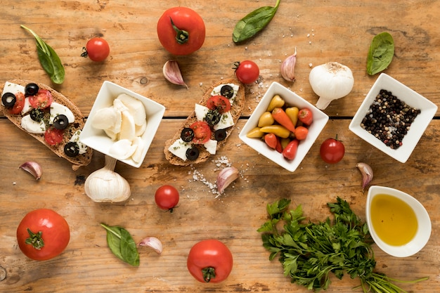 Adorne la bruschetta y el ingrediente fresco para cocinar en la mesa marrón.