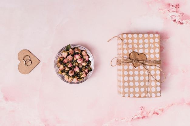 Adorno corazón con anillos cerca de flores en lata y caja de regalo.