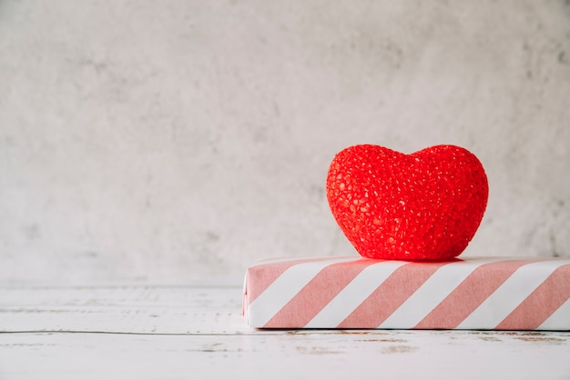 Adorno de corazón cerca de caja de regalo