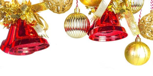 Adorno de navidad, con campanas de navidad rojas y bolas de árbol de navidad doradas sobre blanco