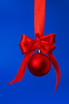 Adorno de navidad colgando de cinta de raso rojo sobre fondo azul.