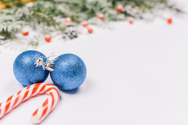 Adornos azules con bastón de caramelo cerca de ramas de abeto