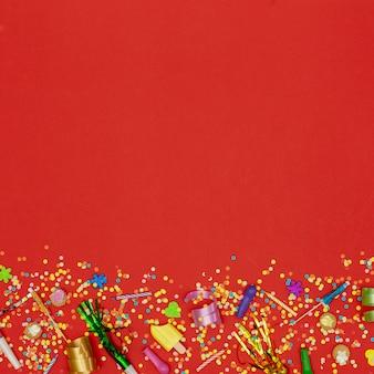Adornos de cumpleaños planos sobre fondo rojo.