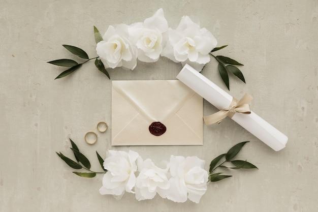 Adornos florales con anillos de compromiso y tarjeta de invitación.