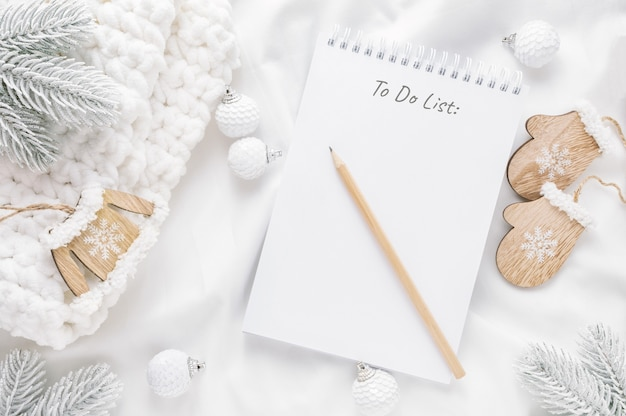 Adornos navideños y bloc de notas con lista de tareas pendientes en blanco