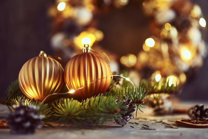 Adornos navideños con bolas doradas, ramas de abeto y guirnaldas de luces sobre un fondo oscuro