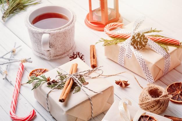 Adornos navideños con cajas de regalo, piñas y una taza de té.