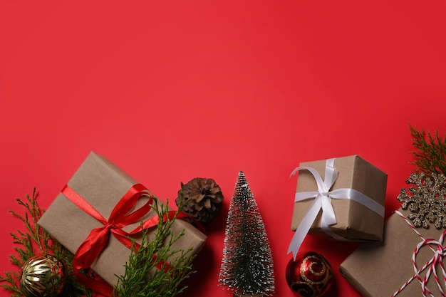 Adornos navideños, cajas de regalos y ramas de abeto sobre fondo rojo. copie el espacio.