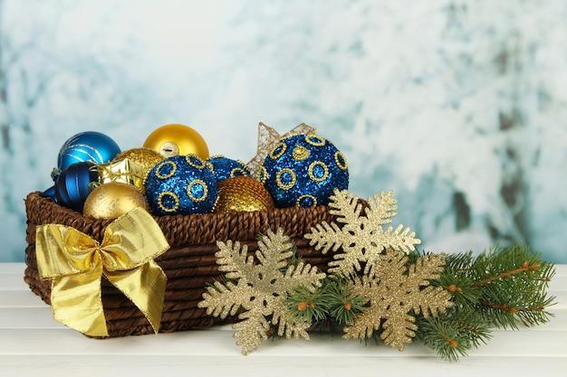 Adornos navideños en canasta y ramas de abeto en mesa sobre fondo brillante