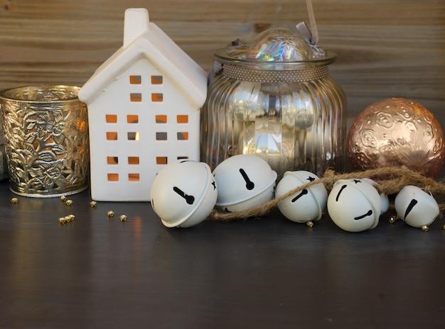 Adornos navideños y casa blanca de invierno con velas brillantes de cerca