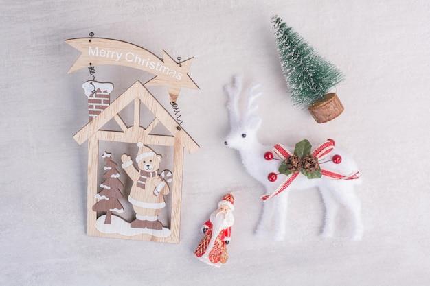 Adornos navideños, ciervos de juguete, pino y santa sobre superficie blanca.