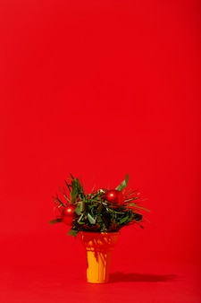 Adornos navideños en cono de helado en pared roja