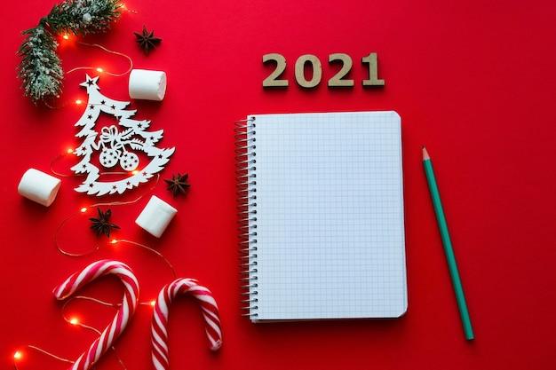 Adornos navideños y cuaderno para escribir metas o resultados del año en rojo brillante