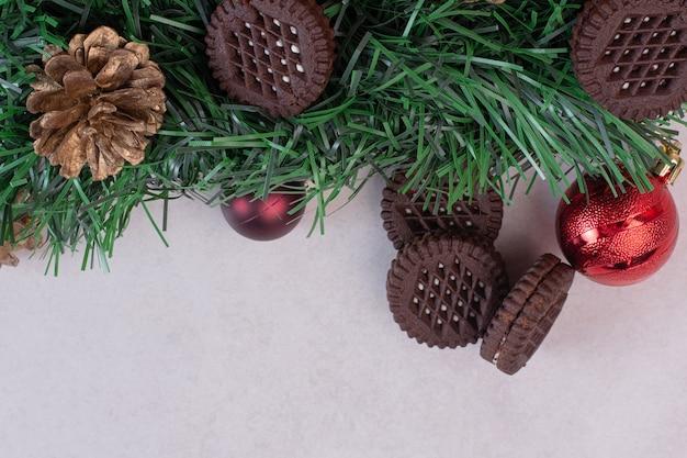 Adornos navideños con galletas en superficie blanca