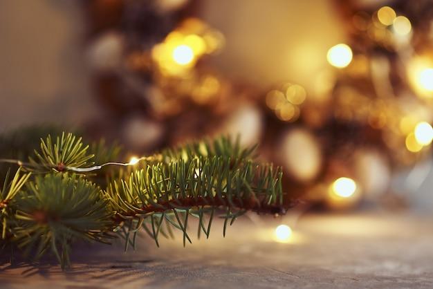 Adornos navideños con luces de guirnaldas y rama de abeto en la oscuridad
