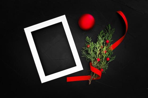 Adornos navideños con un marco con copia espacio sobre un fondo negro