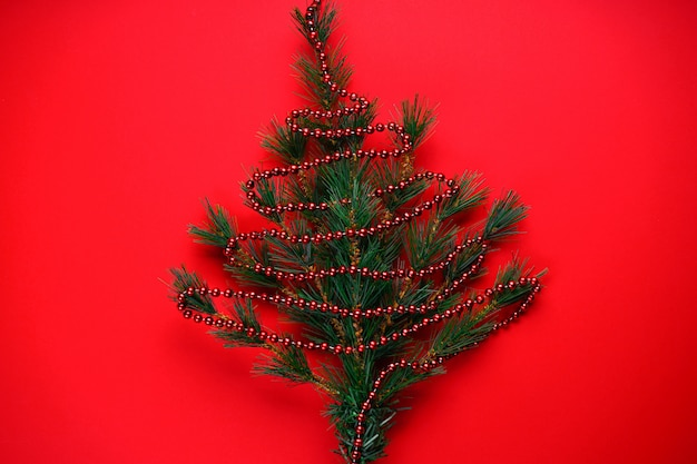 Adornos navideños o navideños: ramas de un árbol de navidad en forma de árbol de navidad con cuentas rojas sobre rojo