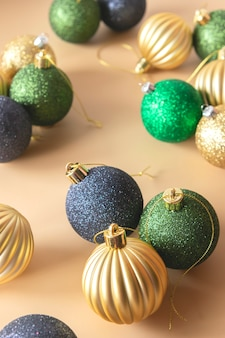 Adornos navideños de oro verde y azul sobre un fondo beige composición navideña festiva
