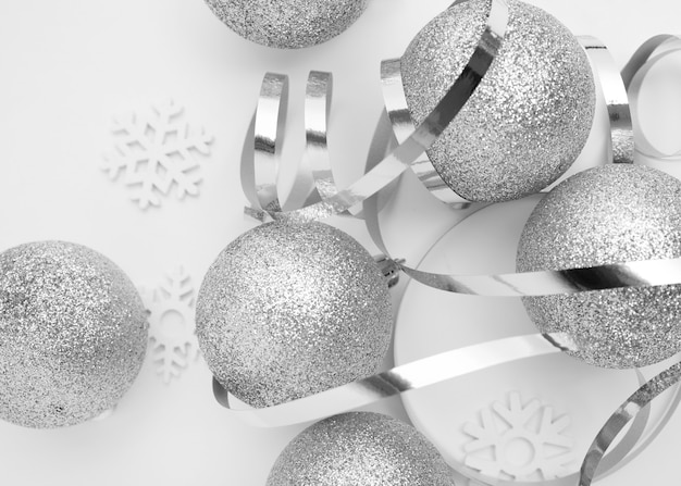 Adornos navideños de plata sobre mesa blanca