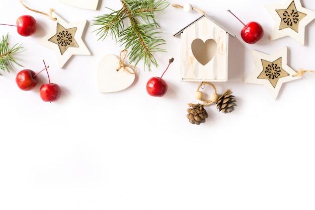 Adornos navideños, ramas de abeto, manzanas rojas sobre fondo blanco.