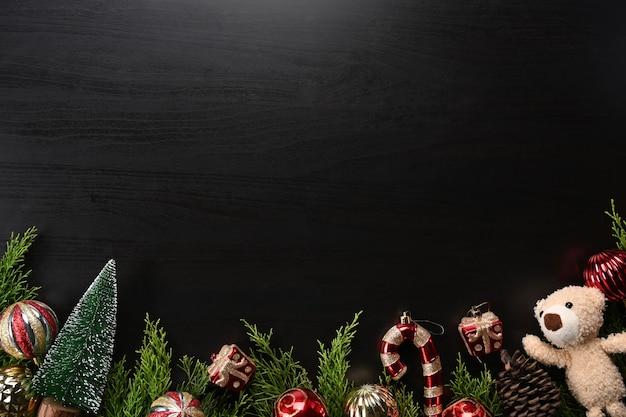 Adornos navideños y ramas de abeto sobre fondo negro.