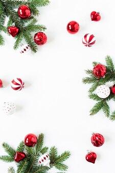 Adornos navideños y ramas de abeto sobre superficie blanca