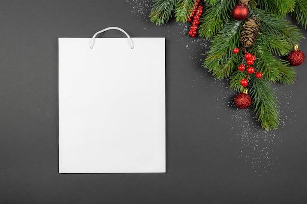Adornos navideños rojos y ramas de abeto con nieve y bolsa de compras de regalo blanco sobre fondo oscuro