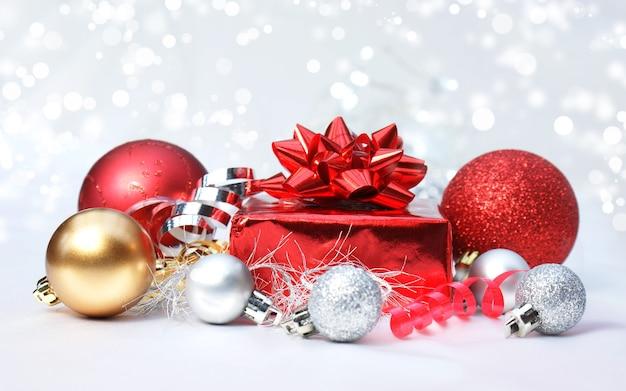 Adornos navideños sobre un fondo de luces plateadas