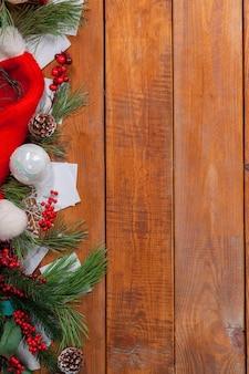 Adornos navideños sobre fondo de madera para tarjeta de felicitación