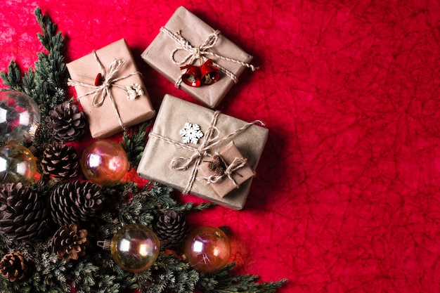 Adornos navideños sobre fondo rojo con regalos envueltos