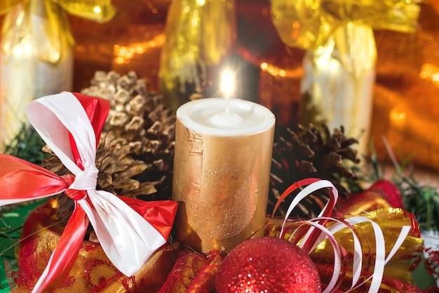 Adornos navideños con velas, pino y cintas.